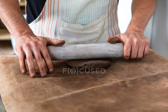 From above of crop unrecognizable male artisan in apron rolling up clay piece at table in traditional workshop — Stock Photo