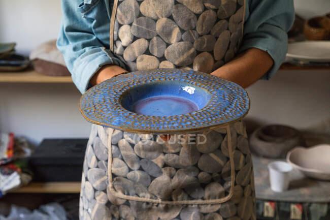 Cultivar artesão irreconhecível em avental demonstrando placa de cerâmica criativa em oficina — Fotografia de Stock