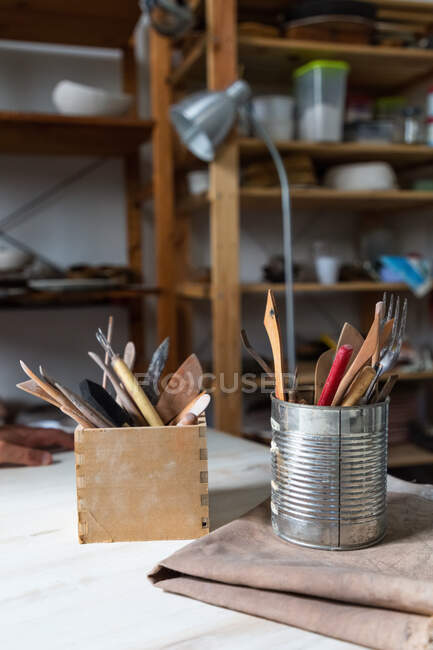 Various pottery tools in metal can and stationery holder placed on table in aged workshop with wooden shelves — Stock Photo