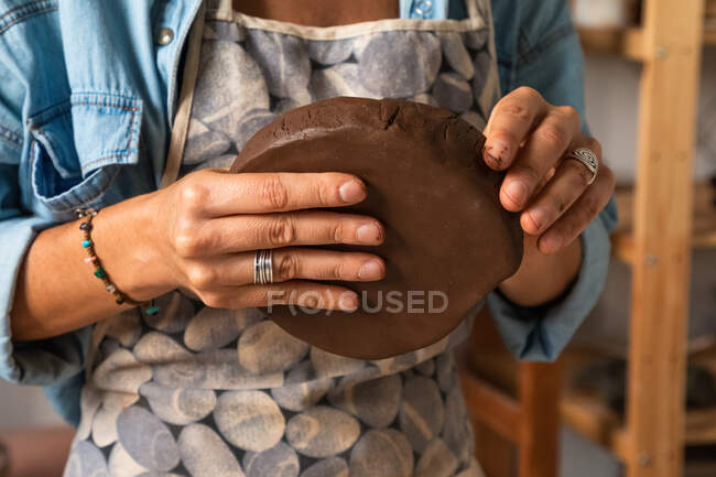 From above of crop anonymous male artisan molding clay piece while creating plate in workshop — Stock Photo
