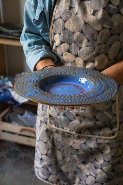 Crop unrecognizable artisan in apron demonstrating creative ceramic plate in workshop — Stock Photo