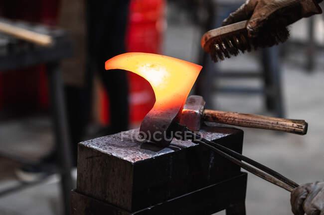 Безликий коваль тримає гарячу металеву деталь сокири вікінга з тонгами під час роботи з дротяною щіткою в кузні — стокове фото