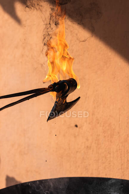 Безіменний ремісник, який витримує гостроту залізної гострої зброї у гарячій воді під час обробки металу. — стокове фото