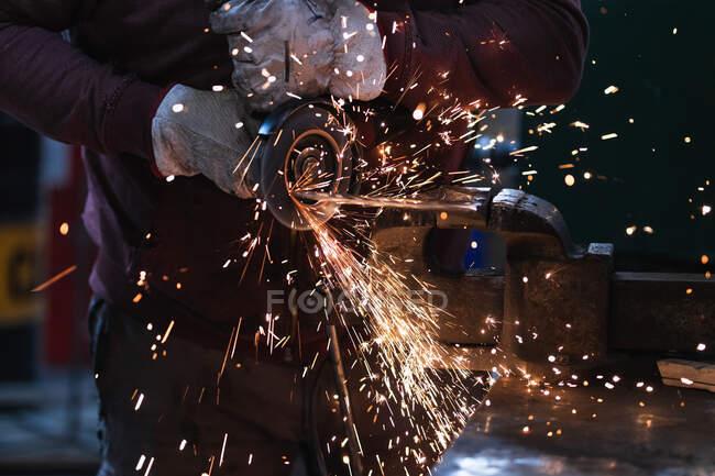 Ernte anonymer Meister in Handschuhen Verarbeitung Eisenprodukt mit Funkenschleifer in Schmiedeeisen eingespannt — Stockfoto