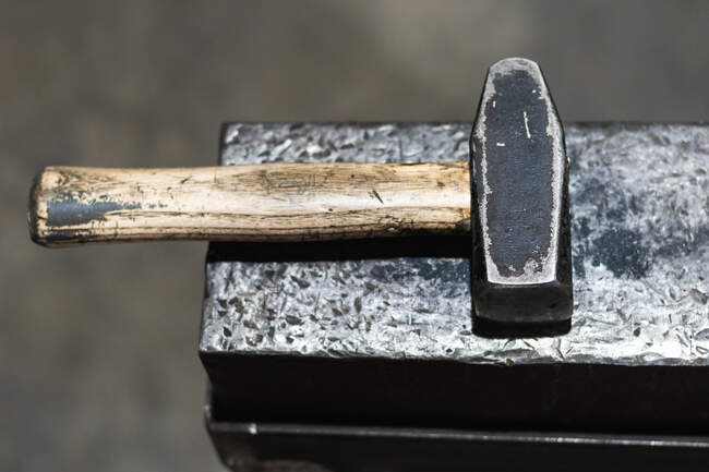 From above of tool with heavy metal head with wooden handle on workbench in forge — Stock Photo