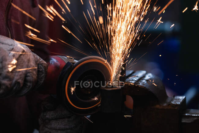 Crop anonymous master in gloves processing iron product with spark grinder clamped in vice in forge — Stock Photo