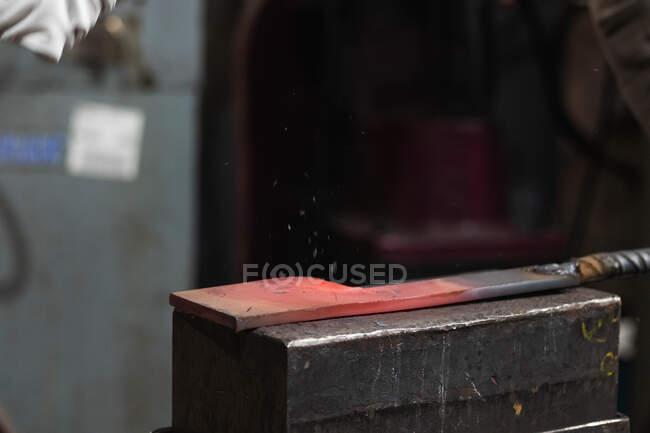Продукт з червоного гарячого металу на важкому коварі для виготовлення і зміни форми в майстерні коваля — стокове фото