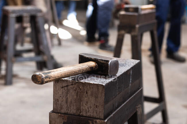 Tool with heavy metal head with wooden handle on workbench in forge — Stock Photo
