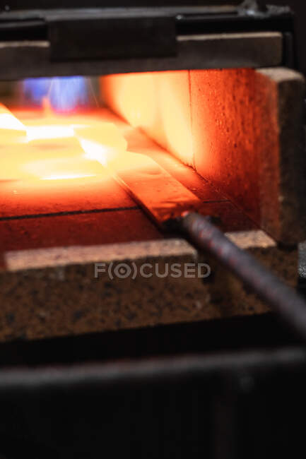 High angle of burning metal tool in melting hot high temperature furnace of smelter — Stock Photo