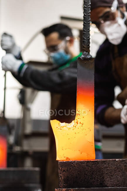Crop anonymous craftsmen in gloves making hot metal detail with hammer in blacksmith workshop — Stock Photo