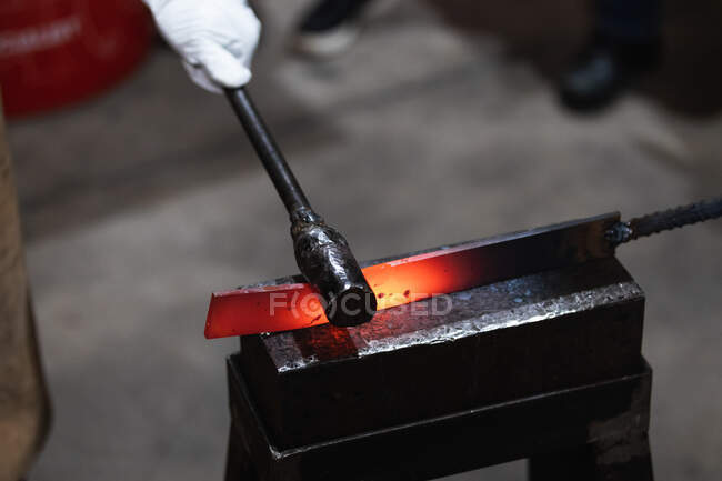 Unrecognizable craftsman hammering hot iron piece at anvil during forging process in workshop — Stock Photo