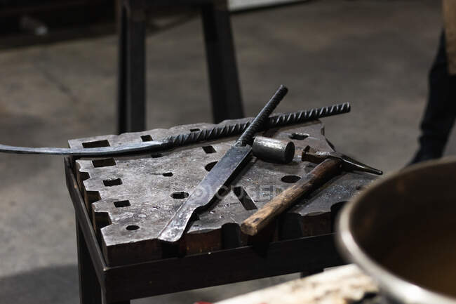 Various metal instruments placed on table in smithy — Stock Photo