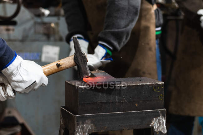 Crop unrecognizable male masters with hammer hitting hot metal detail placed on anvil in forge — Stock Photo