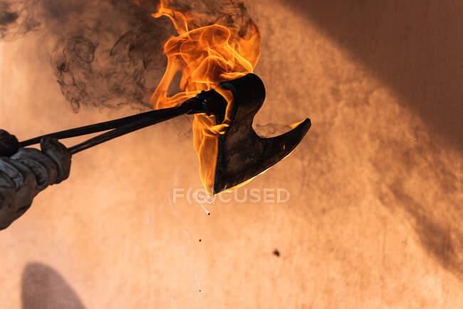 Faceless artisan hardening burning iron sharp weapon in hot water during metal forging process in smithy — Stock Photo