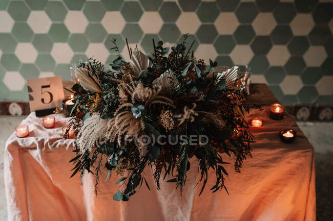 Blooming flowers on tablecloth with number and burning candles against ornamental wall during festive event in cafeteria — Stock Photo