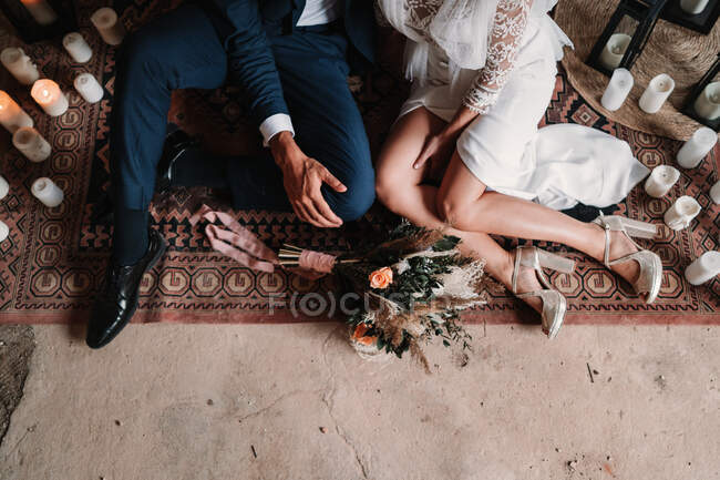 From above cropped unrecognizable young newlywed couple wearing posh wedding clothes sitting on floor on arabic rug — Stock Photo