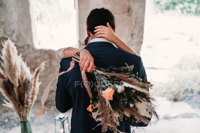 Задній вигляд нареченого в елегантному смокінгу обіймає наречену з букетом на вулиці в сонячний день — стокове фото