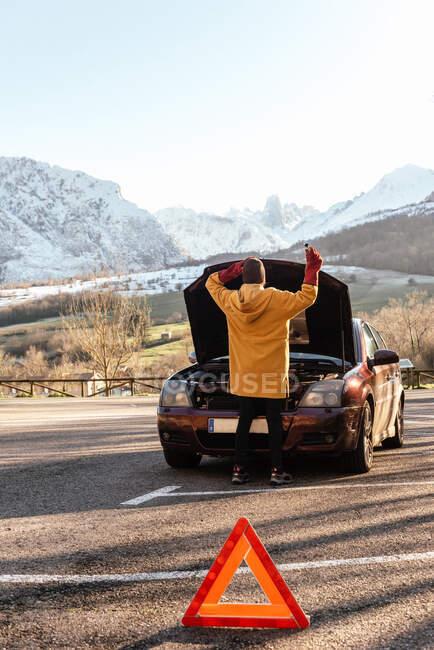 Vista trasera persona de cuerpo entero en abrigo abriendo la capucha del coche aparcado cerca de la señal de carretera triángulo de advertencia en las soleadas tierras altas de invierno - foto de stock