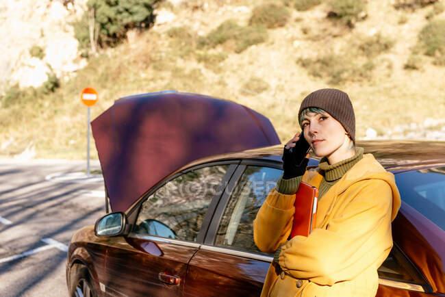 Calma joven mujer en ropa de abrigo que tiene llamada telefónica y se apoya en el coche con la capucha abierta mientras está de pie en el borde de la carretera y mirando hacia otro lado después de la ruptura en el día soleado de otoño - foto de stock