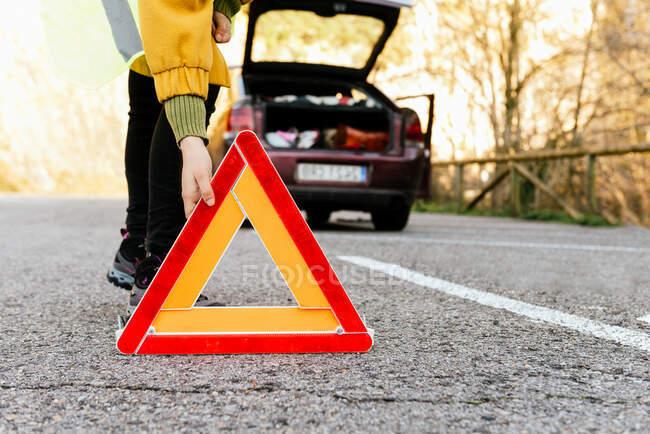 Cultivado irreconocible persona poniendo triángulo de advertencia señal de tráfico en la carretera - foto de stock