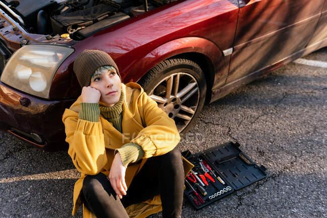 Desde arriba mujer joven y melancólica en ropa de abrigo sentada en asfalto cerca del coche con capucha abierta y caja de herramientas después de la ruptura mientras se apoya de cabeza en la mano y mirando hacia otro lado en contemplación - foto de stock