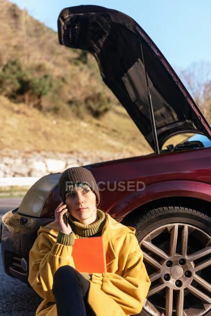Calma joven mujer en ropa de abrigo que tiene llamada telefónica y sentado en el suelo apoyado en el coche con capucha abierta en el borde de la carretera y mirando hacia otro lado después de la ruptura en el día soleado de otoño - foto de stock