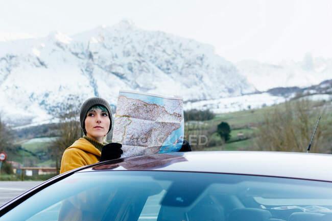 Attraktive junge Frau in Oberbekleidung steht mit Landkarte neben modernem Auto bei Roadtrip im schneebedeckten bergigen Gelände an kalten Wintertagen — Stockfoto