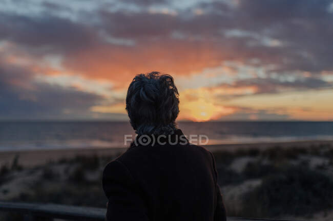 Back view of elderly female traveler in casual clothes standing on wooden pier on sandy beach and enjoying seascape at sunset — Stock Photo