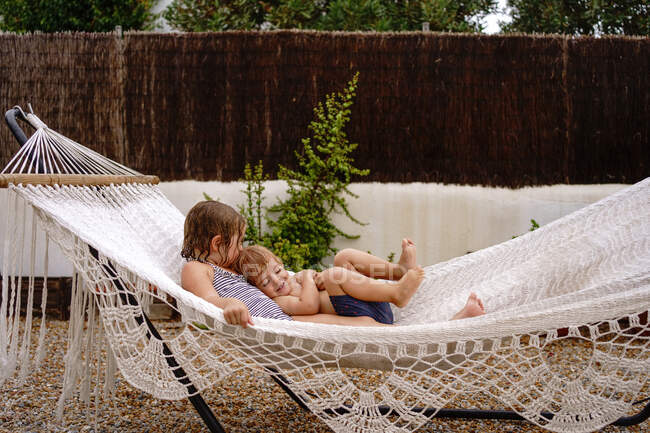 Cute barefooted little sister and brother hugging while lying in hammock and having fun during summer holidays — Stock Photo