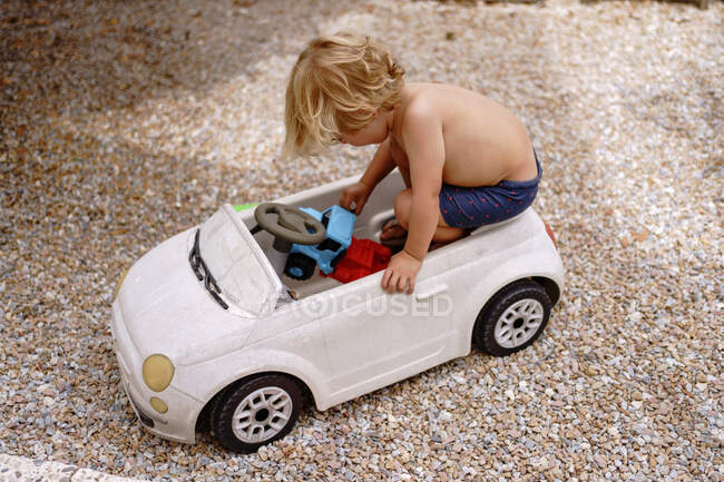 Side view of cute cheerful little boy with blond hair riding toy car while laying in yard on sunny summer day — Stock Photo