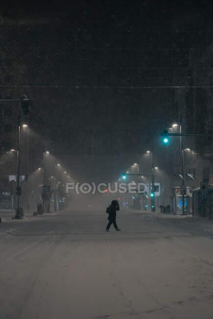 Vista lateral del hombre anónimo en ropa interior caminando por la carretera en invierno nevado en Madrid España - foto de stock