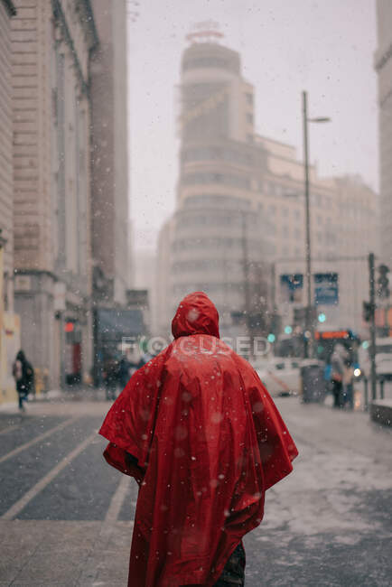 Back view of anonymous male in bright red protective cloak walking on street with buildings in snowy winter in Madrid Spain — Stock Photo