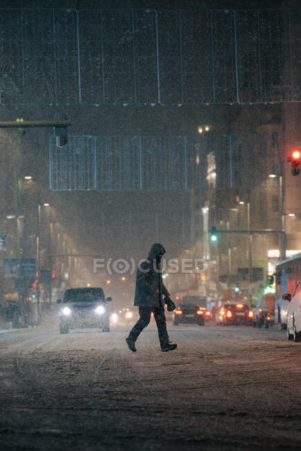 Side view of anonymous man in outerwear walking on roadway with transport in winter in Madrid Spain — Stock Photo