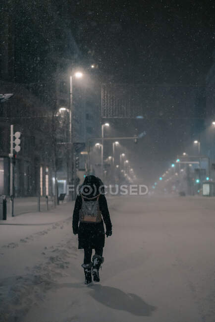 Back view of anonymous man in outerwear walking on roadway in snowy winter in Madrid Spain — Stock Photo