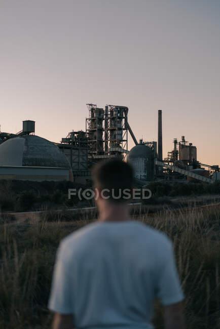 Vista posterior del hombre anónimo borroso en el prado contra la central eléctrica bajo el cielo gris en el campo de la noche - foto de stock