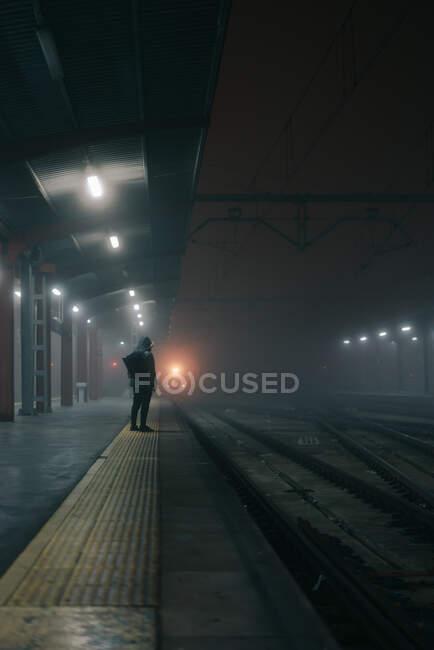 Повернення до нерозпізнаного туриста з рюкзаком чекає на поїзд на платформі під блискучими лампами у сутінках. — стокове фото