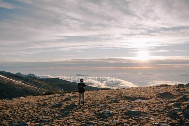 Vista posteriore dell'esploratore irriconoscibile turista maschio in tuta calda con zaino in piedi contemplando la montagna sotto spesse nuvole all'alba — Foto stock