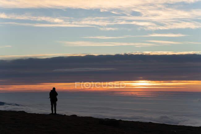 Vista trasera de explorador irreconocible turista masculino en ropa interior cálida con mochila de pie contemplando la montaña bajo densas nubes al amanecer - foto de stock