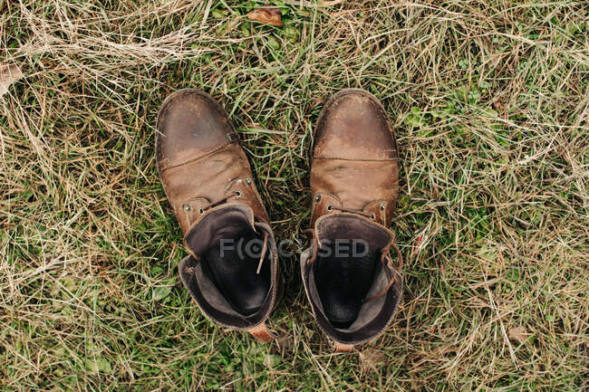 Top view of pair of worn brown leather shoes placed on grassy lawn in nature — Stock Photo