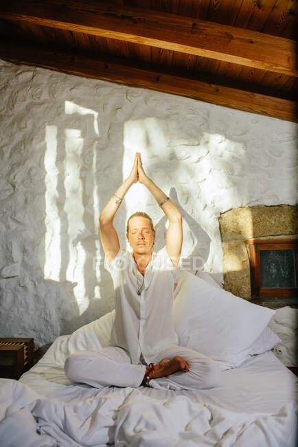 Блондин, сидящий на кровати, практикуя медитацию — стоковое фото