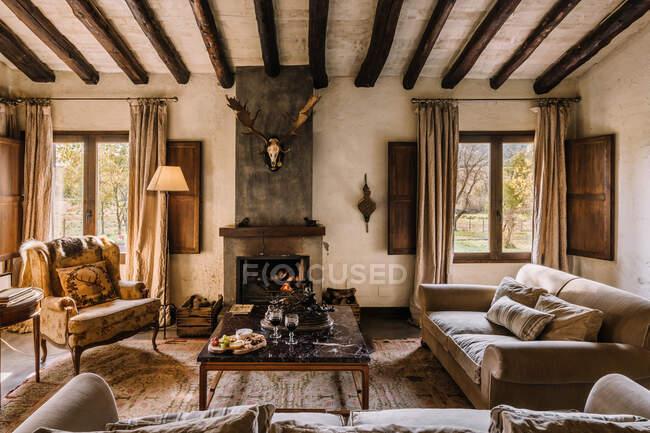 Простої вітальні з диваном і м'якими подушками біля столу і каміном у мисливському будинку. — стокове фото