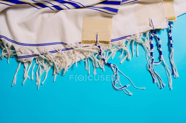 Vista superior del chal con adorno a rayas que representa el concepto de viaje sobre fondo brillante - foto de stock