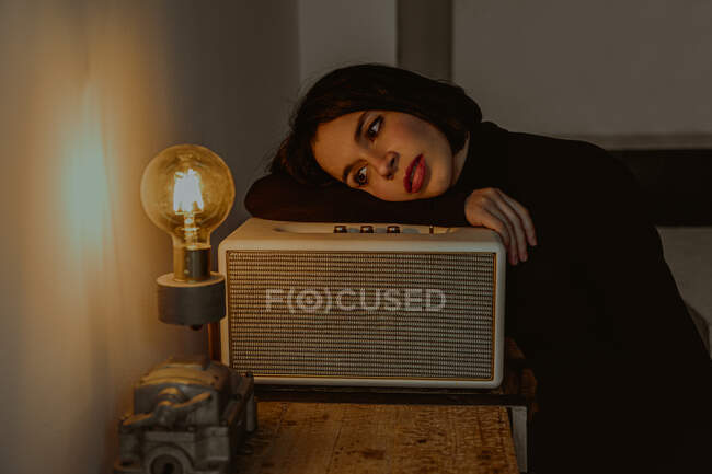 High angle of dreamy female leaning on radio set in retro room and looking at illuminated light bulb — Stock Photo