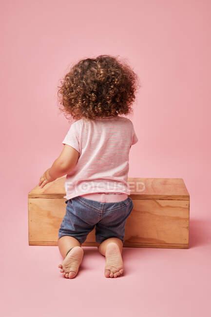 Vista posterior de niño descalzo irreconocible en camiseta y pantalones cortos de mezclilla con pelo rizado jugando en la plataforma de madera - foto de stock