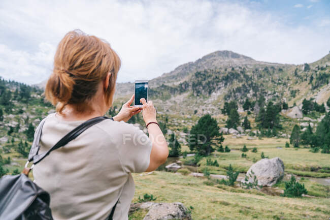 Back view anonymous female backpacker taking pictures on smartphone of amazing stony verdant highlands in Ruda Valley in Catalan Pyrenees — Stock Photo