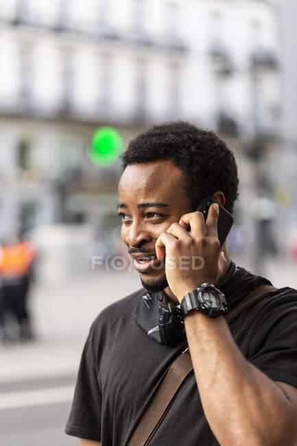 Jeune homme afro-américain contenu dans la montre-bracelet parler sur un téléphone portable tout en regardant ailleurs en ville — Photo de stock