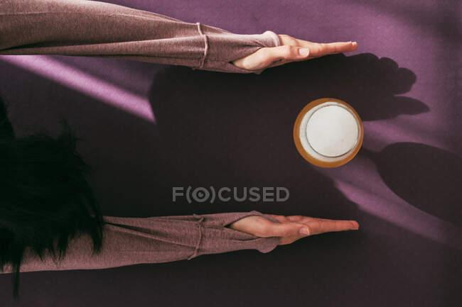 Vista dall'alto dello yoga femminile anonimo in posa estesa per bambini su stuoia con vetro di birra a casa — Foto stock