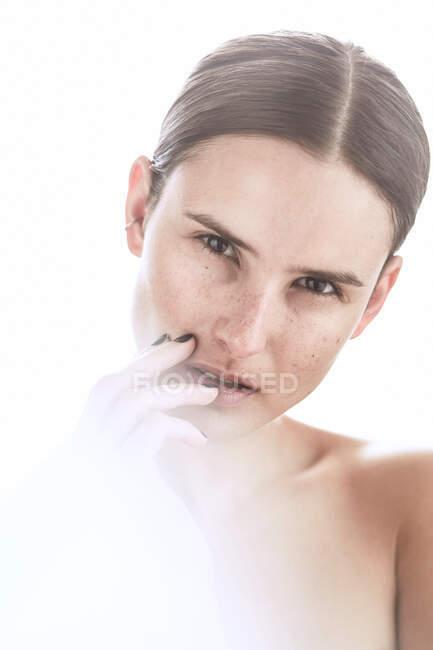 Серьёзная женщина с макияжем и веснушками на носу нежно касается кожи и смотрит в сторону — стоковое фото
