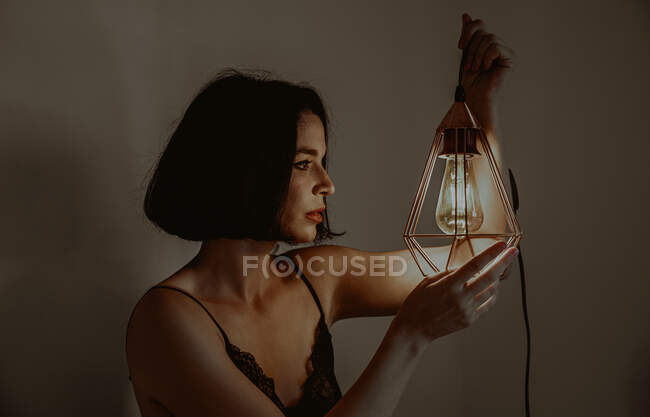 Side view of delicate female touching illuminated metal lantern while sitting in room at home — Stock Photo