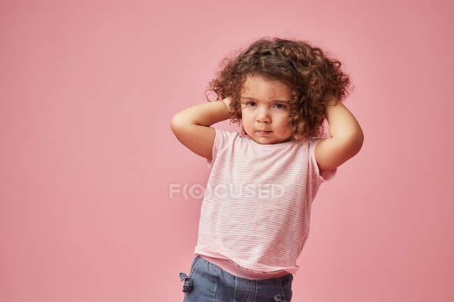 Niño descontento en ropa casual con el pelo rizado cubriendo las orejas mientras mira hacia otro lado - foto de stock